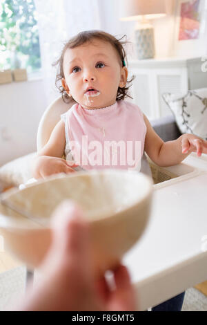 Mother feeding baby daughter in high chair - Stock Photo