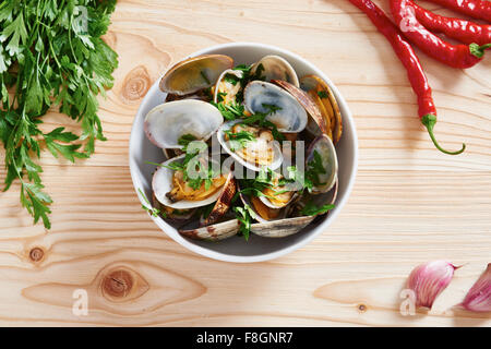 Steamed Clams in white bowl on wooden table - Stock Photo