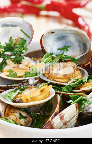 Close-up of Steamed Clams in white bowl on wooden table - Stock Photo