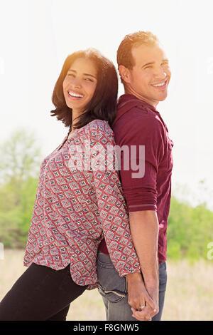 Hispanic couple standing back to back - Stock Photo