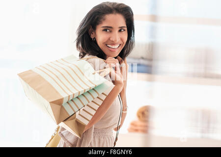 Hispanic woman carrying shopping bags - Stock Photo