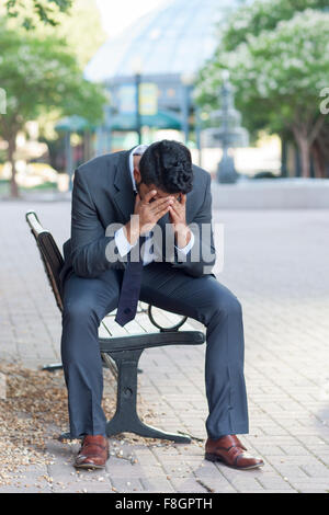 Frustrated Indian businessman sitting on bench - Stock Photo