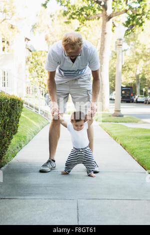 Father helping baby son walk on sidewalk - Stock Photo