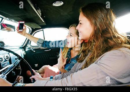 Friends taking selfie in vintage car - Stock Photo
