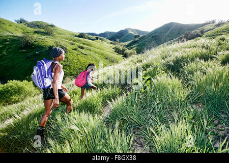 Black mother and daughter walking on rural hillside - Stock Photo