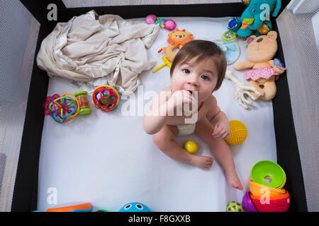 Mixed race baby girl sitting in playpen - Stock Photo