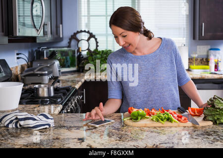 Mixed race woman reading recipe on cell phone in kitchen - Stock Photo