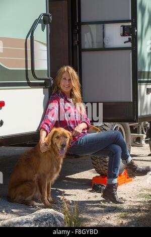 Caucasian woman petting dog at trailer - Stock Photo