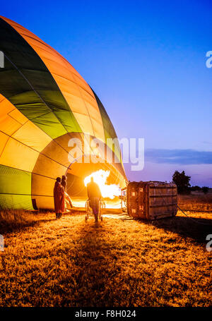 Hot air balloon inflating in rural field - Stock Photo