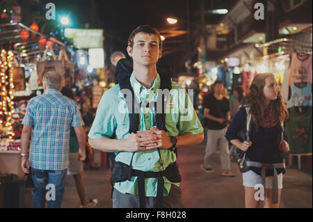 Caucasian tourist standing in market at night - Stock Photo
