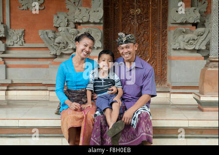Asian mother, father and son smiling outside ornate building - Stock Photo