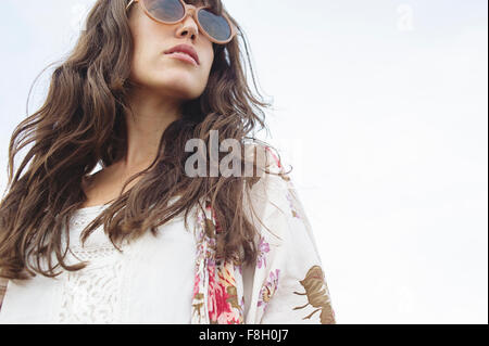 Low angle view of Caucasian woman wearing sunglasses outdoors - Stock Photo