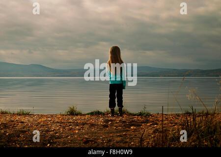 Caucasian girl standing at lake - Stock Photo