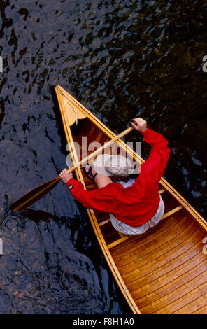A young woman in a bright red jacket paddles a vintage wooden canoe in a stream. MODEL RELEASED - Stock Photo