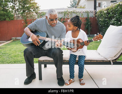 African American grandfather teaching granddaughter to play guitar - Stock Photo