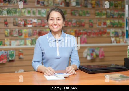 Woman selling seeds in store for gardeners - Stock Photo