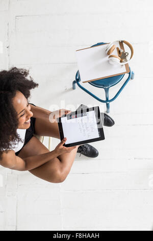 A young Afro-American woman using a tablet or iPad in a studio type setting - Stock Photo