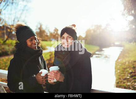 Two girlfriends looking at camera and smiling while standing on bridge, holding coffee to go, river on background - Stock Photo