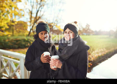 Two young women standing on bridge and holding coffee to go, smiling - Stock Photo