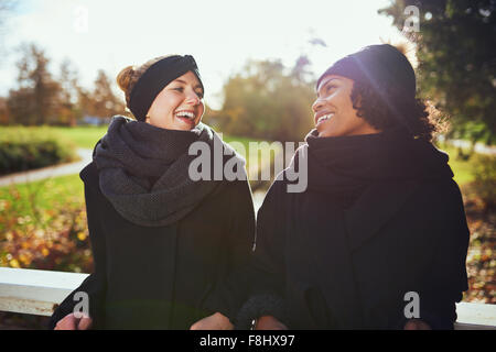 Two women in warm clothes standing on bridge in park and smiling at each other - Stock Photo