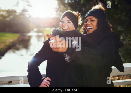 Two girlfriends laughing at something while standing in park against of river. - Stock Photo