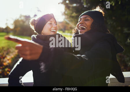 Two women laughing at something while standing in park - Stock Photo