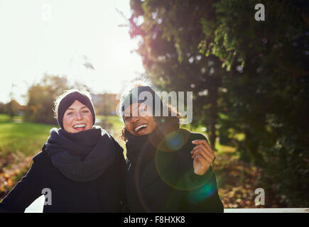 Two smiling women standing on bridge in park.Sunny - Stock Photo