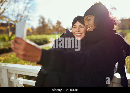 Two smiling young women in warm clothes taking selfie against of autumnal park - Stock Photo