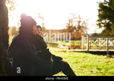 Two young women sitting in autumnal park, leaning on tree trunk.Sunny - Stock Photo