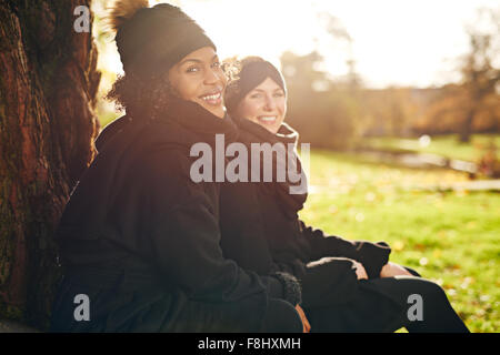 Two young women sitting in autumnal park and smiling at camera.Sunny - Stock Photo