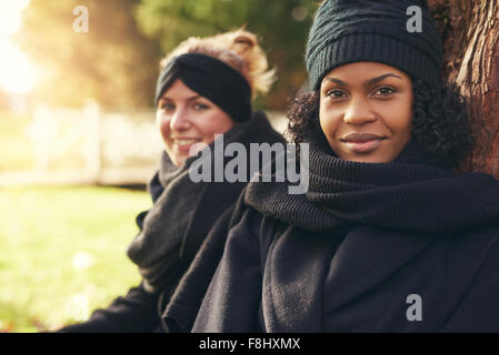 Close-up of two smiling young women leaning on tree trunk in autumnal park - Stock Photo