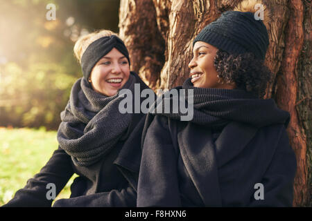 Close-up of two smiling young women leaning on tree trunk in autumnal park and looking at each other - Stock Photo