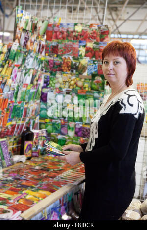 Female gardener buys the seeds in market - Stock Photo