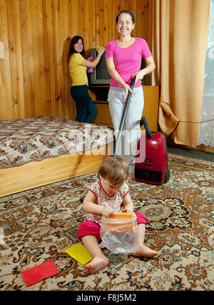 The family cleans in living room with a vacuum cleaner - Stock Photo