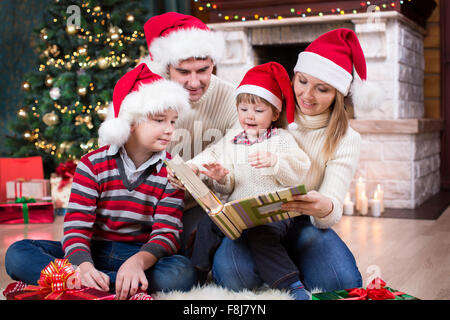 Family reviewing their photos in album near Christmas tree in front of fireplace - Stock Photo