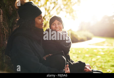 Two smiling young women sitting in park and leaning on tree trunk.Sunny - Stock Photo
