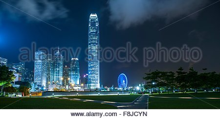 Sky line and ferris wheel illuminated at night, financial district, Hong Kong, China - Stock Photo