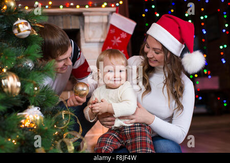 Happy family with child decorating Christmas tree in front of fireplace  in living room - Stock Photo