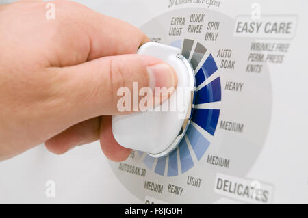 Laundry washing machine dial being set by a person's hand - Stock Photo