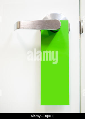 A green hanging door handle sign on a hotel room door to indicate green water conservation initiative - Stock Photo