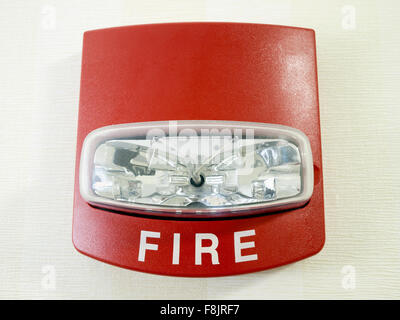 Red fire alarm strobe light smoke detector mounted on a wall as part of a commercial fire protection system - Stock Photo