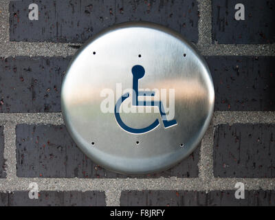 Handicapped disabled access automatic door opener button switch with a wheelchair symbol on a brick wall - Stock Photo