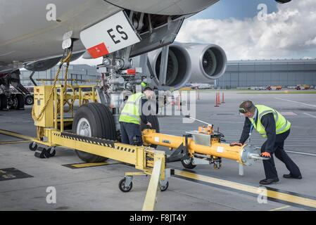 Ground crew fixing tow bar onto A380 aircraft at airport - Stock Photo