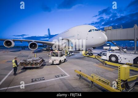 Ground crew attach tug to A380 aircraft on stand at dusk at airport - Stock Photo