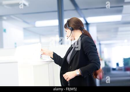 Telephonist working in office - Stock Photo