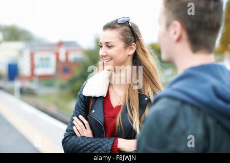 Young woman  and young man standing on railway platform - Stock Photo