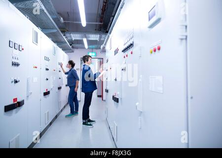 Full length side view of colleges in control room back to back looking at switchgear - Stock Photo