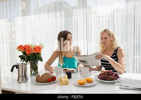 Women sitting at dining table enjoying a continental breakfast together, reading newspaper - Stock Photo