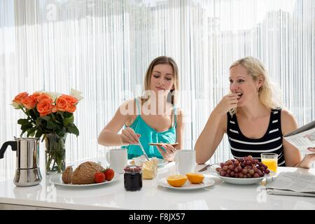 Women sitting at dining table spreading butter on bread, eating a continental breakfast together - Stock Photo