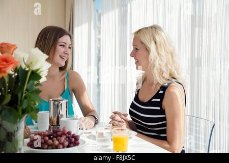 Women sitting at dining table enjoying a continental breakfast together, face to face smiling - Stock Photo